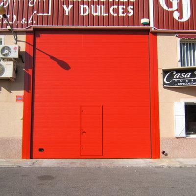 Puerta Seccional industrial roja con peatonal insertada