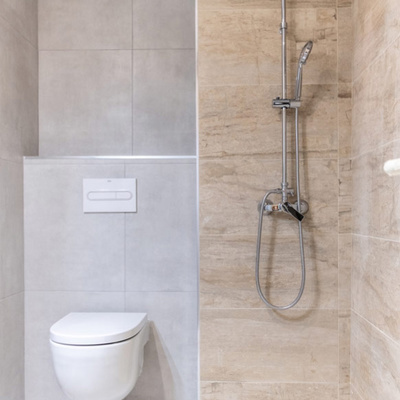 Inodoro suspendido y ducha con contraste de alicatado