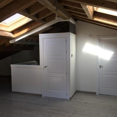 Puerta integrada en pared de cristal bajo techo de madera