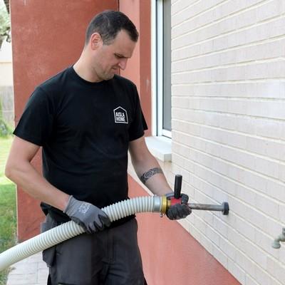 Técnico de AISLAHOME insuflando una vivienda por el exterior.