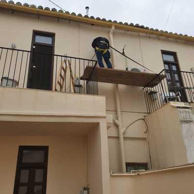 Instalación de unidades exteriores en fachada de vivienda con andamios y arnes de seguridad