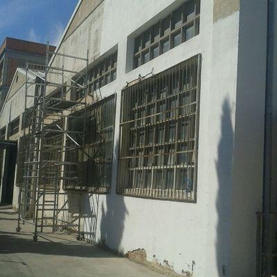 Pintado fachada fabrica con paredes con luminarias de cristal  y rejas.Vista I