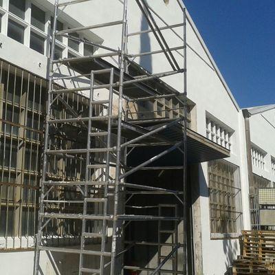 Pintado fachada fabrica con paredes con luminarias de cristal  y rejas.Vista II