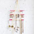 colgador de collares hecho con hilos y madera