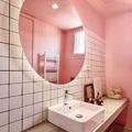 Baño rosa con espejo redondo