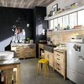 Cocina con mobiliario de madera y paredes de pizarra
