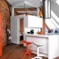 Cocina en blanco y naranja con pared ladrillo vista
