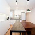 Cocina en Forma de L y con isla compuesta por una barra de hierro y mesa de madera