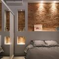 dormitorio con hornacinas de obra y pared de ladrillo visto