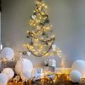 árbol de navidad con guirnaldas en la pared