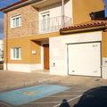 Puerta de entrada en pvc color madera, ventanas en PVC blanco, y puerta de garaje