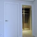 Puerta lisa lacada, embocadura de paso y armario gabanero sin puertas.