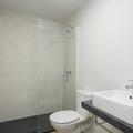 Baño moderno con encimera de mármol, mampara de cristal fija y radiador de baño