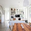salón con Tv colgada y estanterías metálicas