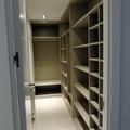 Vestidor sin puertas en acabado lino en habitación estrecha.