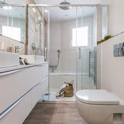Baño moderno con plato de ducha y bañera.