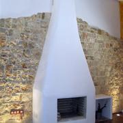 Chimenea terminada con pared de piedra e iluminación