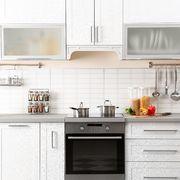 Cocina blanca con armarios y barras para accesorios