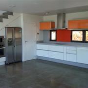 Cocina blanca con toques en colores y aprovechamiento del bajo de escalera