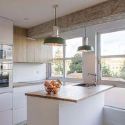 Cocina blanca y de madera con grandes ventalaes