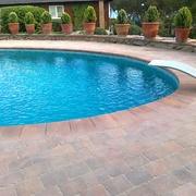 Coronación piscina mediante losa mismo color al adoquín
