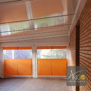 Distribuidores Recasens - Cerramiento con techo fijo de panel sándwich y toldos verticales perimetrales
