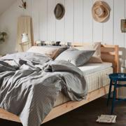 Dormitorio con cama de madera y colchón de muelles.