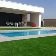 Construcción de piscina desbordante con cesped artificial modelo DIAMANTE en su perímetro