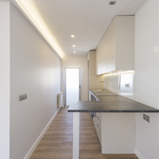 Cocina abierta con encimera de mármol en L, iluminación LED y mobiliario moderno