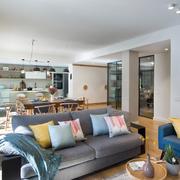 Salón abierto a la cocina con puertas de vidrio y suelos de madera