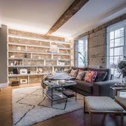 salón con gran librería de pladur sobre pared de ladrillo