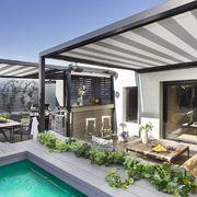 Terraza con piscina, zona de comedor y barbacoa.