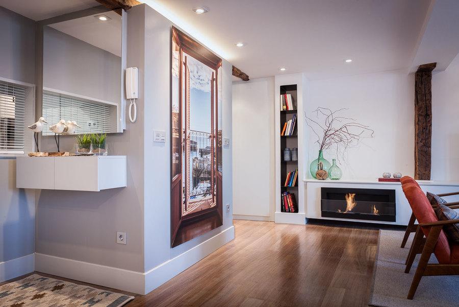 A la izquierda, espejo sobre mueble en el hall de entrada, a la derecha chimenea en el salón