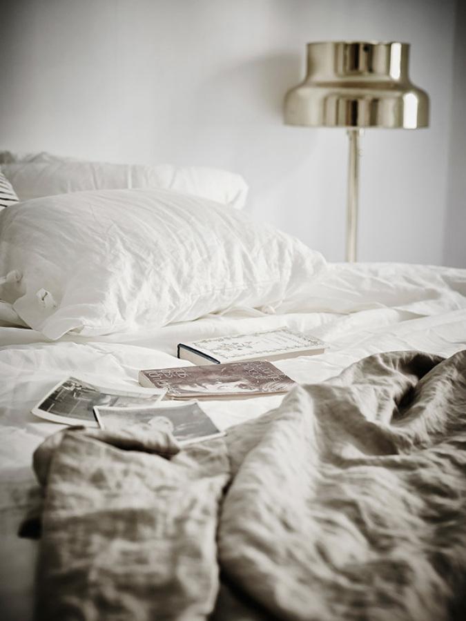 cama deshecha con libros encima