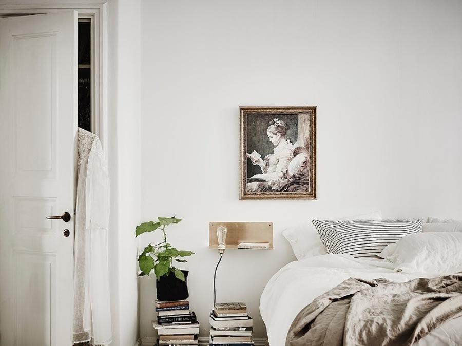 dormitorio con libros que hacen de mesita de noche