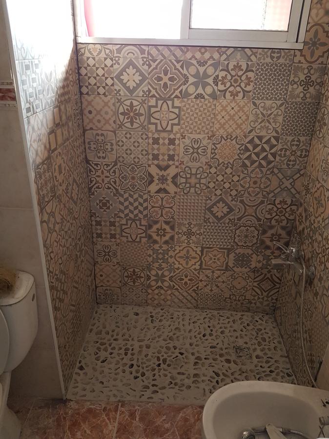 azulejos y plato ducha de obra con piedras