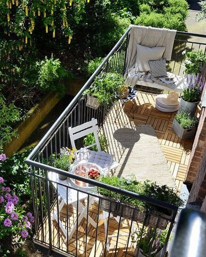 Balcón pequeño con cojines y flores