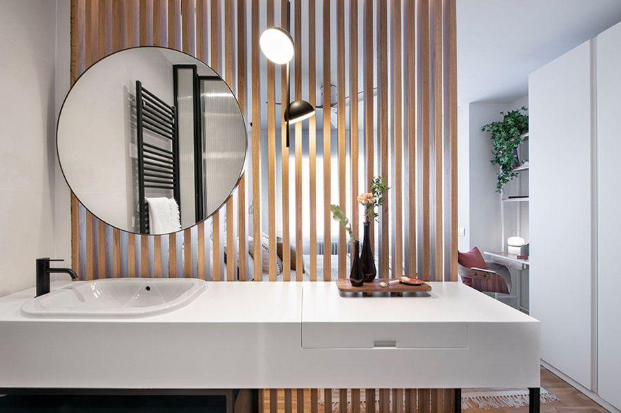 Baño abierto al dormitorio con paneles de madera