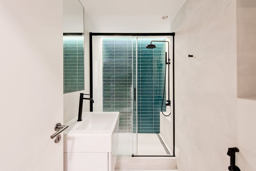 Baño blanco con ducha y grifería en negro