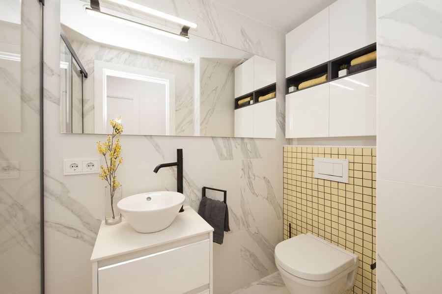 Baño blanco con grifería en negro y detalles en amarillo