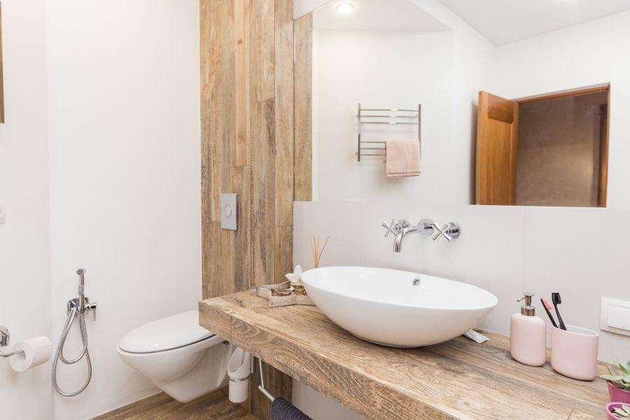 Baño blanco y de madera con lavabo ovalado