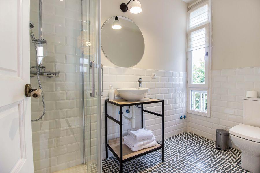baño con azulejo tipo metro y suelo de inspiración hidraulica con plato de ducha.