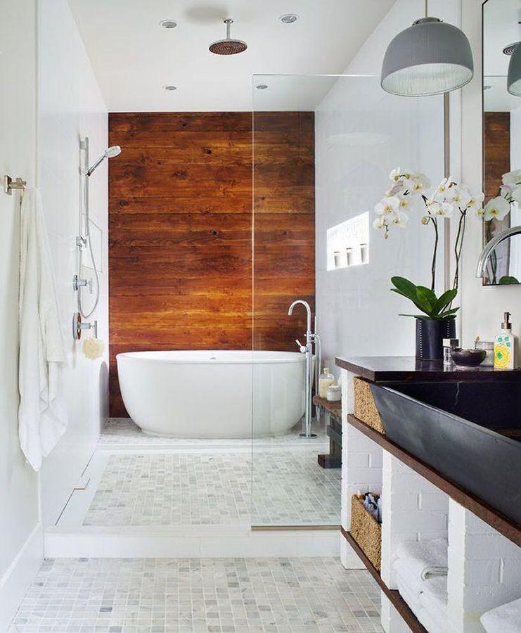 Baño con bañera y pared de madera