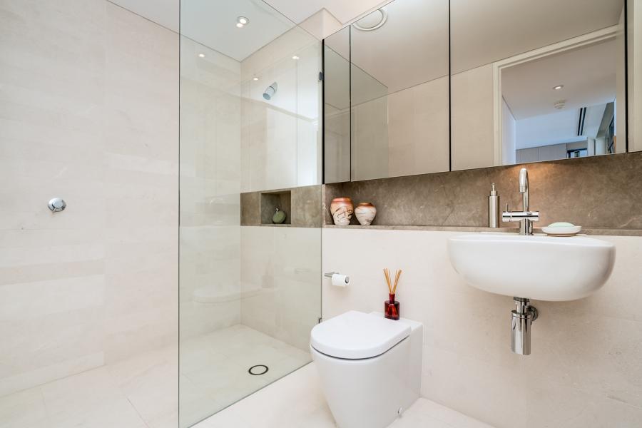 Baño con ducha y pavimiento de mármol