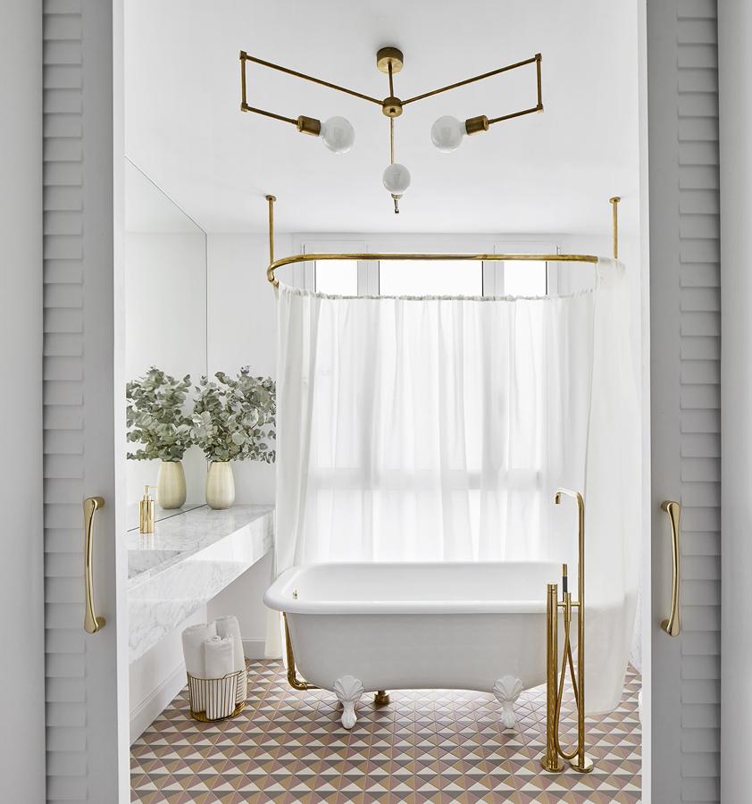baño con gran bañera exenta y detalles dorados de Miriam Barrio