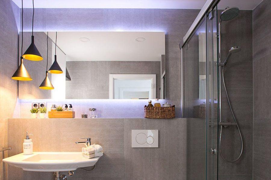 Baño con lámparas colgantes, luces LED y efectos retroiluminados