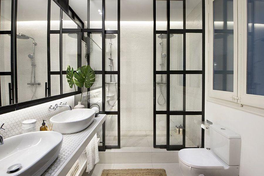 Baño con mampara puertas de cristal y perfilería negra