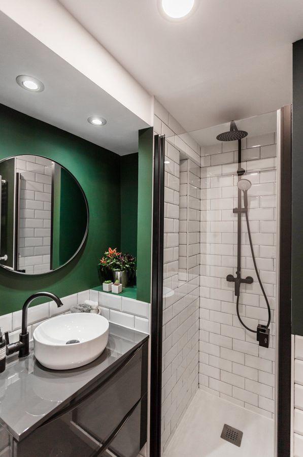 Baño con pared en verde y focos empotrados