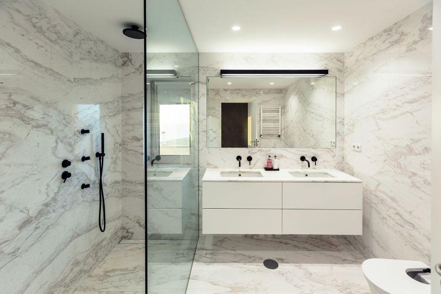Baño con revestimientos de mármol, ducha y fijo de cristal