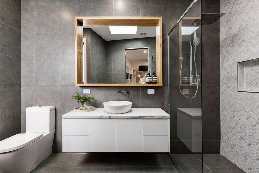 Baño con revestimientos porcelánicos y mueble lavabo suspendido.